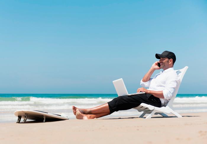 homem na praia, aproveitando a vida, enquanto fala ao telefone para resolver as questões da empresa que faz dropshipping.