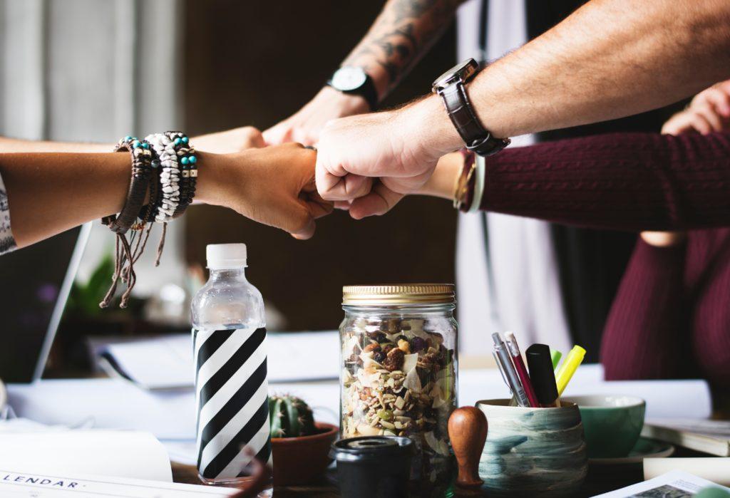 grupo se cumprimentando em cima de mesa de negócios para representar redes de marketing multinível